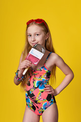 Fashion sunny photo in studio.Portrait girl in colorful suits for beach,swimsuit,holds ice cream picture.Pretty adolescent 10 years.Concept vacation,summer day,beach.Beautiful face child,advertising.