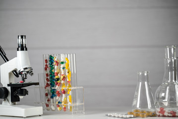 Laboratory Microscope, pills and test tubes. Scientific and healthcare research background.
