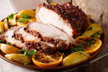 Homemade Hot Pork Tenderloin with Spices with a garnish of potatoes, oranges and apples close-up. Horizontal