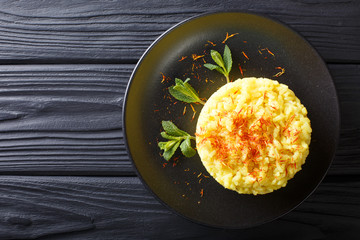 Delicious Italian risotto with saffron and mint (Risotto alla milanese) closeup. horizontal top view from above