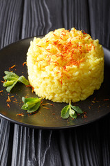 traditional risotto alla milanese with saffron is decorated with mint closeup on a plate. vertical