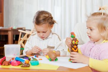 Preschoolers molding figurines from plasticine .