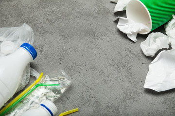 Waste with a plastic bottle, plastic and paper on a gray background, top view. Empty space for text.