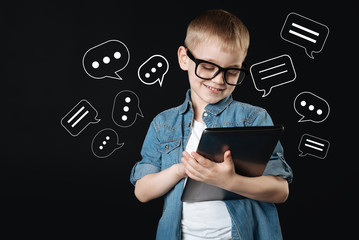 Typing messages. Cheerful cute smiling child kindly looking at the screen of a big modern tablet while typing messages on it