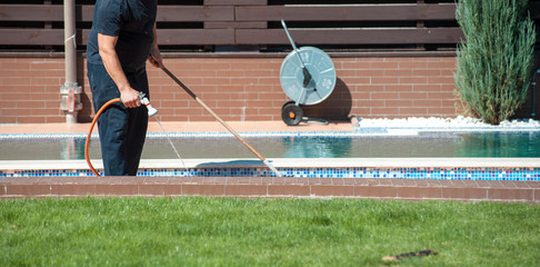 Man clean swimming pool with hose in hands outdoors