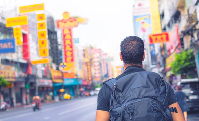 back of a backpacker exploring yaowarat road in Bangkok , Thailand , Southeast Asia .