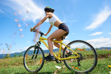 Wide angle view of athlete female biker riding on yellow mountain bicycle on a rural trail, against blue sky with clouds. Outdoor sport activity