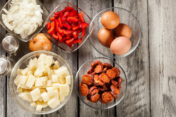 Tortilla de patatas. Ingredients for preparing spanish omelette with sausage chorizo, potatoes, paprika and egg
