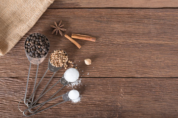 Food ingredient for cooking on a wooden board. Measuring spoons with salt, sugar, coriander seed and black pepper.