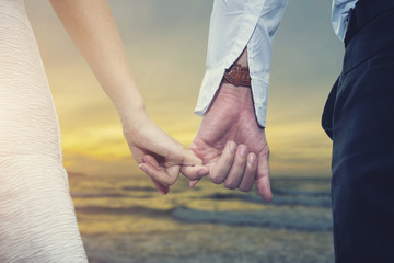 Valentine, love and wedding concept. Closeup of loving couple holding hands while walking on the beach at sunset. Picture for add text message. Backdrop for design art work.