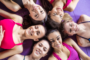 Sports friendship. Six beautiful smiling sportive women lie head to head on the floor in the gym and have fun looking at the camera