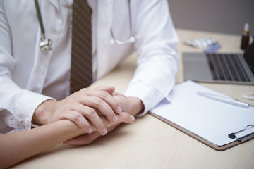 Health care concept. Doctor holding hand of patient to talking and encourage in hospital or clinic. Picture for add text message. Backdrop for design art work.
