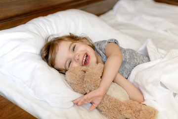 Active adorable baby wakes up lying in bed with her Teddy bear toy, soft white linens. Children's day. World Smile Day. Start the morning right! Start the morning with a smile!