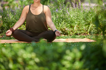Unrecognizable obese woman wearing top and leggings sitting in lotus position on yoga mat and meditating, sunny public park on background