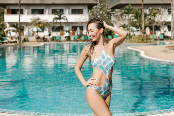 smiling girl posing in swimsuit at swimming pool on tropical resort