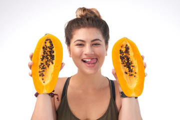Head and shoulder portrait of attractive young woman holding ripe halves of papaya in hands and licking lips, isolated on white background
