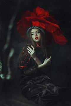 Beautiful model rose hat  is posing in a dark studio