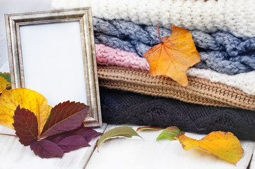 Autumn concept, Stack of warm sweaters,  an empty picture frame,  decorated  with colorful autumn leaves on the wooden table