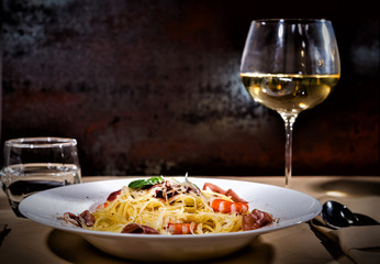 Glass with wine near appetizing spaghetti pasta with shrimps, grated cheese, jamon, tomato sauce and basil in white plate