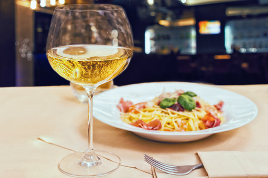 Close up of glass with wine near tasty spaghetti pasta in a restaurant
