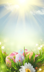 Easter holiday scene background. Traditional painted colorful eggs in spring grass over blue sky. Spring holidays Easter backdrop