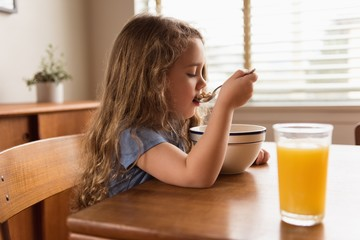Girl having breakfast cereal and juice on table