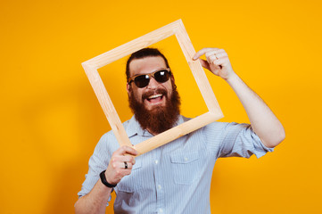 Smiling bearded hipster man in casual with sunglasses into a wooden frame
