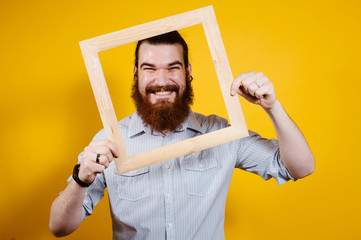 Cheerful smiling bearded man looking through wooden frame