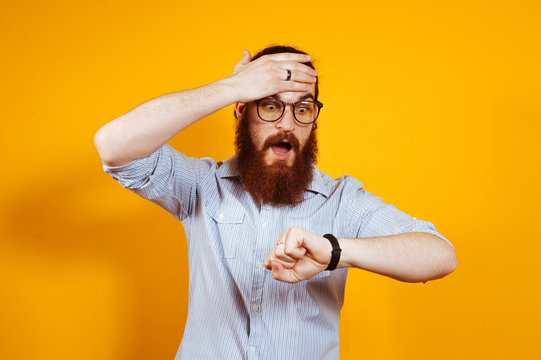 Bearded hipster man with eyeglasses in casual looking shocked at watch, You are late.