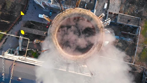 Aerial view of an industrial pipe pollutes the air next to people