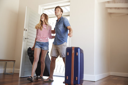 Couple Arriving At Summer Vacation Rental