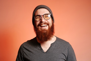 Close up portrait of happy smiling bearded hipster man with eyeglasses and looking confident at the camera