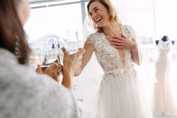 Bride toasting champagne with friends in bridal boutique