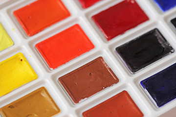 Watercolors and brushes. A palette of multi-colored watercolor paints. Hobbies and creativity. Drawing and Art