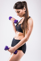 Muscular woman doing exercises with dumbbells at biceps.
