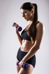 Sporty woman does the exercises with dumbbells on white background. Young woman in sportswear on white background. Strength and motivation.