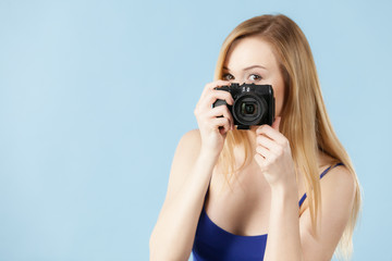 Blonde woman with camera on blue