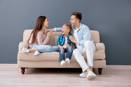Happy family sitting on sofa, indoors