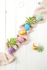 Multicolored easter eggs of pastel and gold color on a white wooden table..