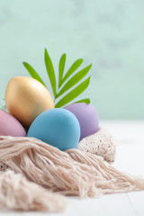 Easter eggs pastel and golden colors on a white wooden table..