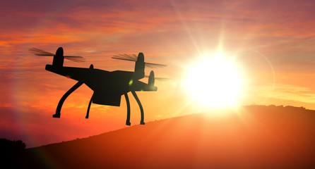 Drone silhouette flying towards sun.