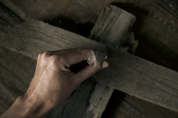 man driving a nail on a wooden cross