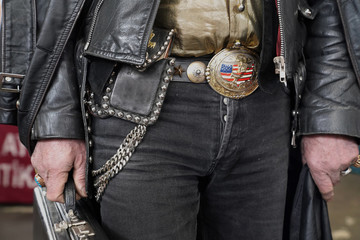 Modern cowboy with leather jacket and leather belt with buckle in the manner of american flag