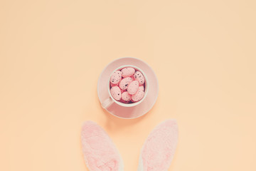 Easter holiday background with bunny ears and easter eggs in coffee cup