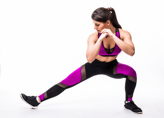 Beautiful young hispanic woman doing lunge exercise in fitness gym over white background