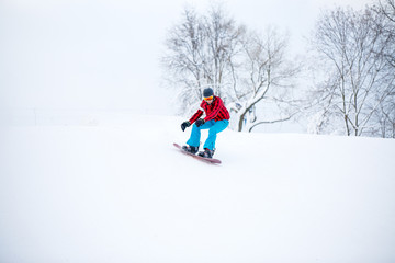 Image of snowboarder man jumping on snowy hill