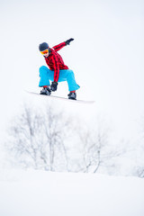 Photo of sportive male snowboarder jumping on snowy hill