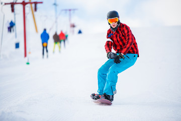 Photo of athlete with snowboard riding in snowy resort