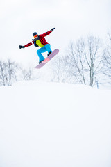 Photo of sportive man in helmet with snowboard jumping in snowy resort