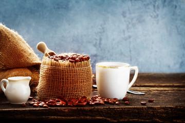 Tasse Kaffee, Kaffeebohnen und Milch auf Holztisch